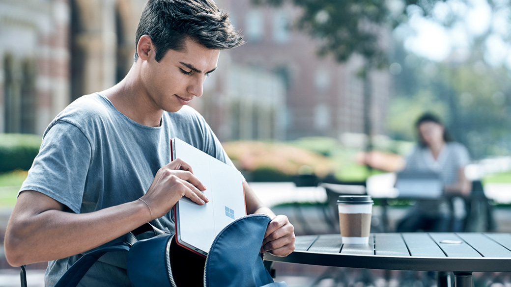 Student works outside on a Surface Pro 4.