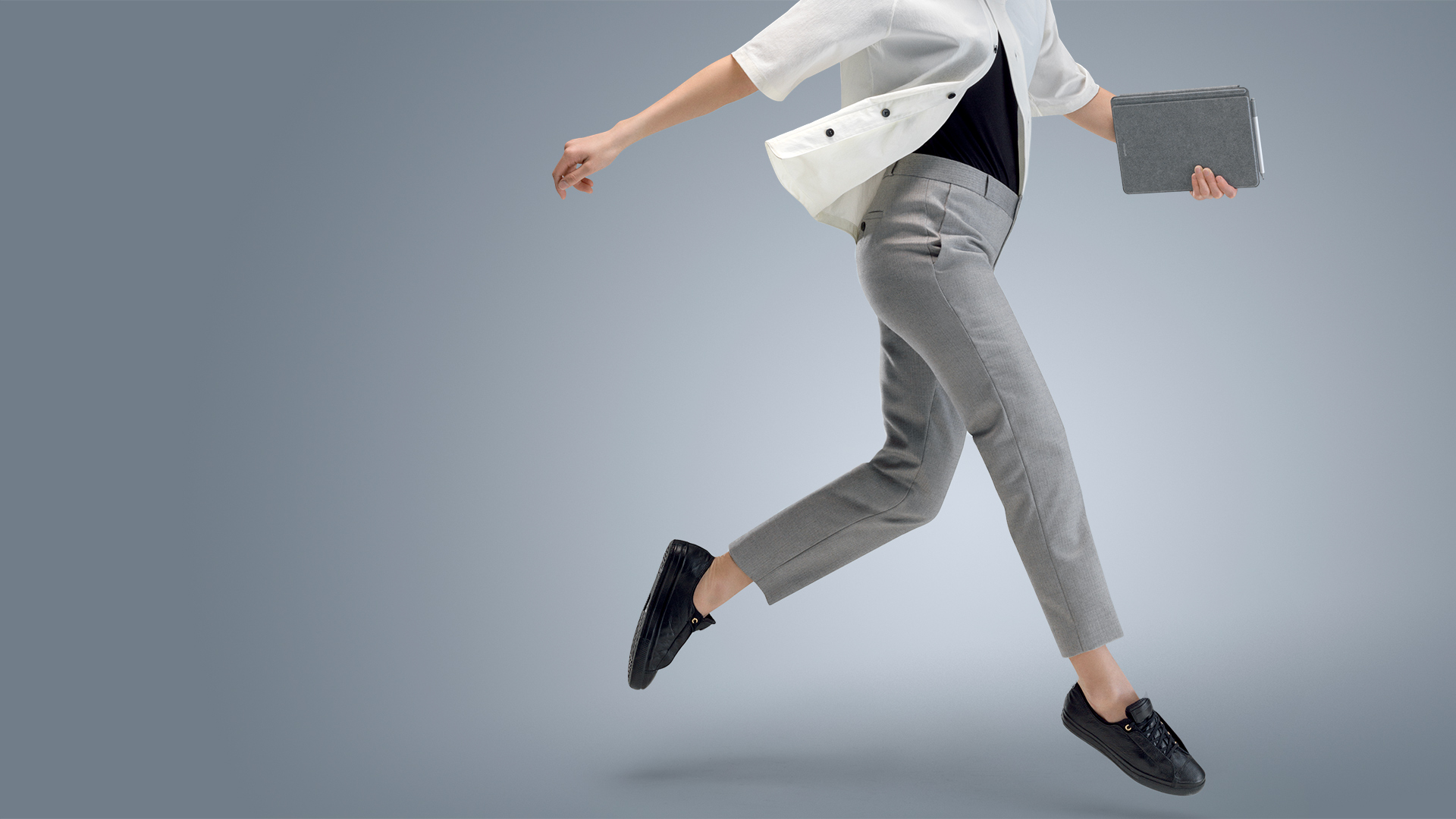 A woman leaps as she carries Surface Go in tablet mode in one hand