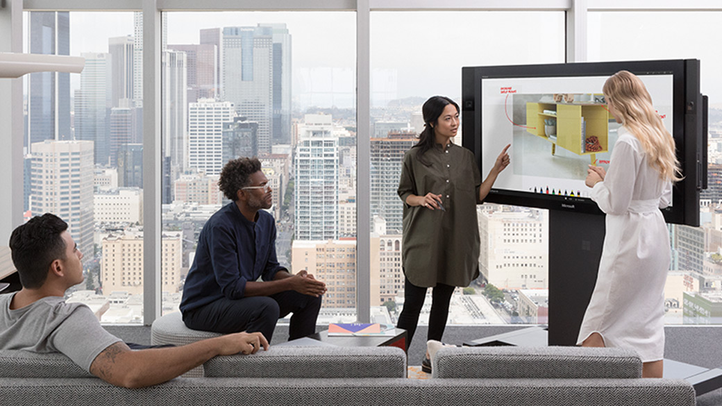Four people stand around a Surface Hub collaborating together.