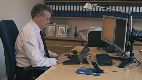 Man typing on a Surface device at a desk in an office.