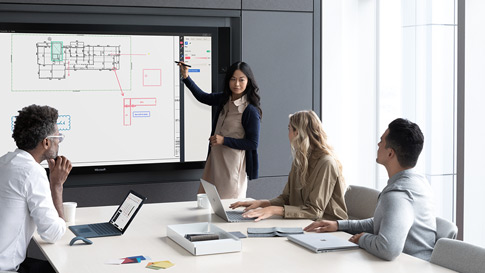 Woman presents on Surface Hub to colleagues in board room.