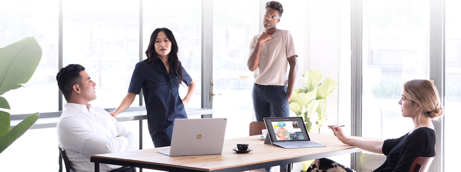 Team gathers around a conference table with Surface devices