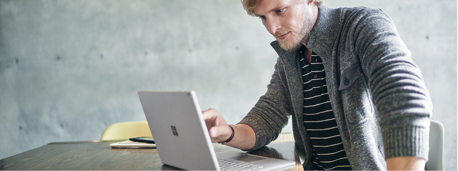 Man uses touchscreen on Surface Book.