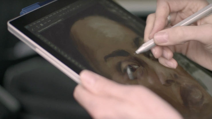 Woman uses Surface Pen to do a detailed drawing of a man's face on a Surface Pro in tablet mode.
