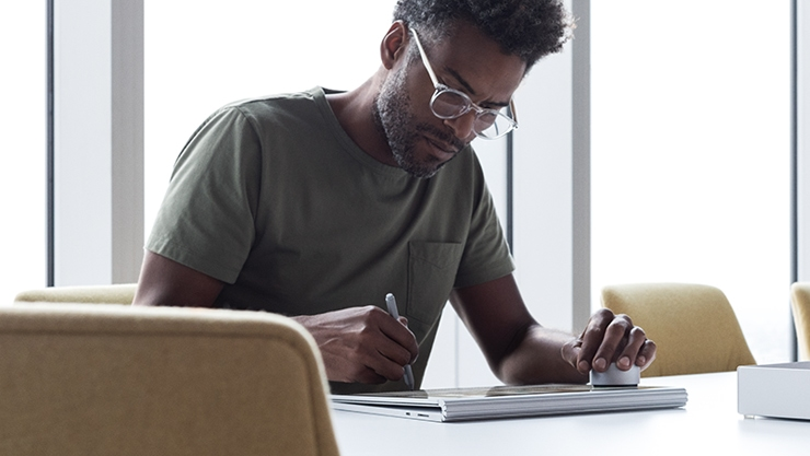 Man uses a Surface Pen on a Surface Book 2 in clipboard mode.