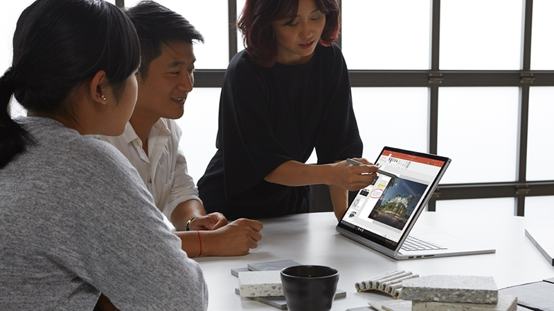Co-workers gather around a conference table and look at a PowerPoint presentation on Surface Book 2 in view mode.