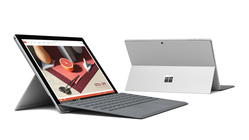 Two Surface Pro computers, one seen from the front left and the other seen from the back, with Surface Pen