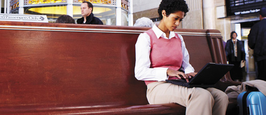 A woman in a train station working on a laptop, learn about Exchange Online Protection features and pricing