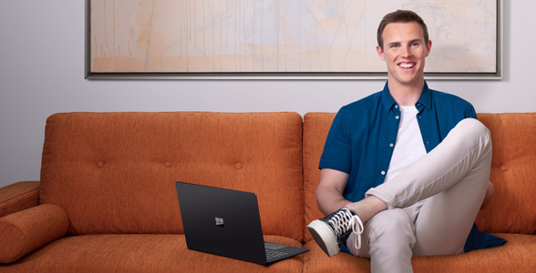 Man sitting on couch with Surface device.