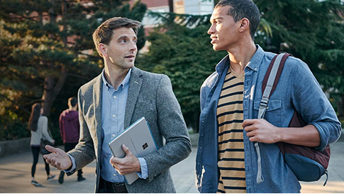 Two men walking and talking with one clutching a back pack and the other holding a Surface Pro 4