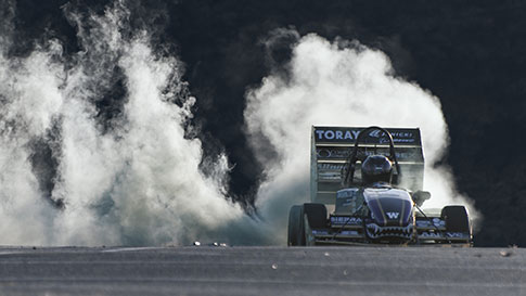 Formula type racecar spinning its wheels and smoke rising behind it