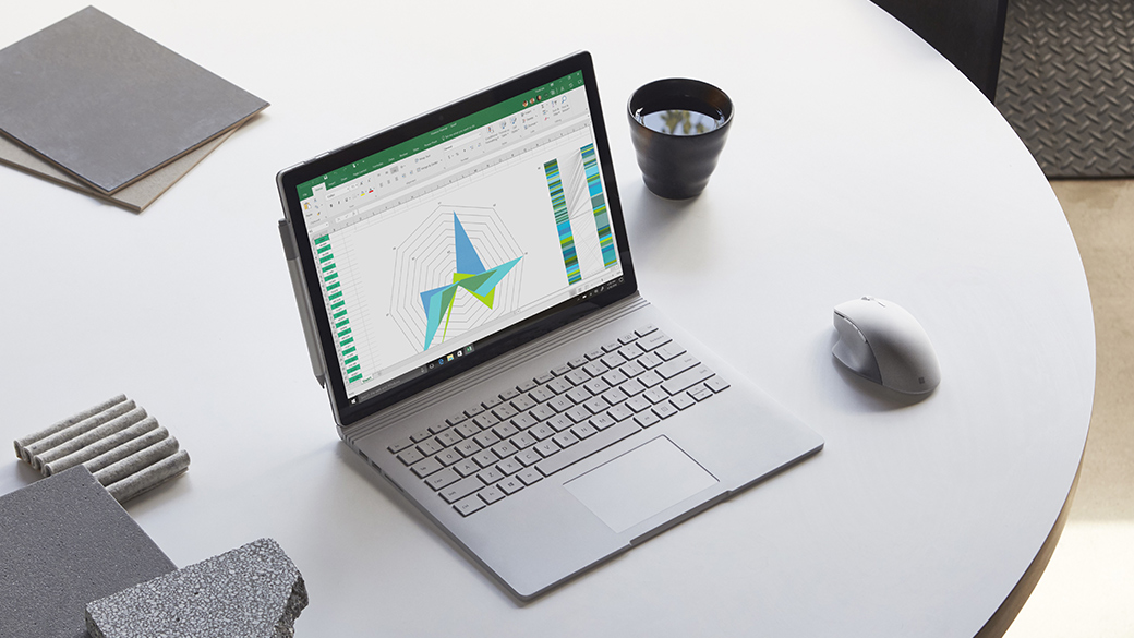Surface Book 2 in a workspace with a Surface mouse and files