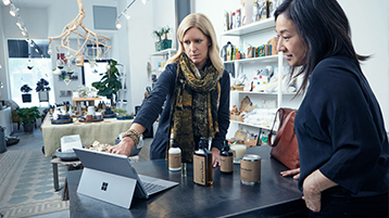 Woman pointing to the screen of a Surface Pro 4 in a boutique, while another woman watches intently