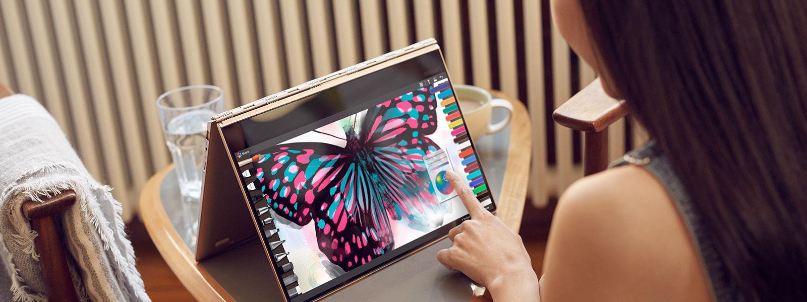 Woman using the touchscreen of a Lenovo YOGA 910