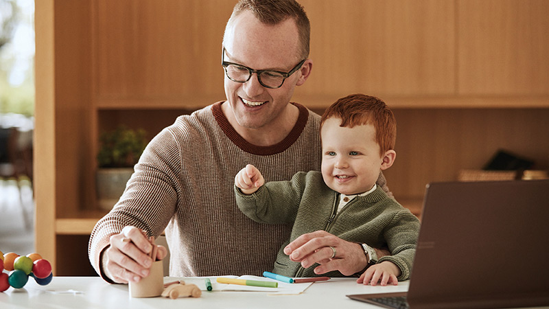 A man holds a young boy on his lap as they play with office supplies and an open laptop computer on a desk