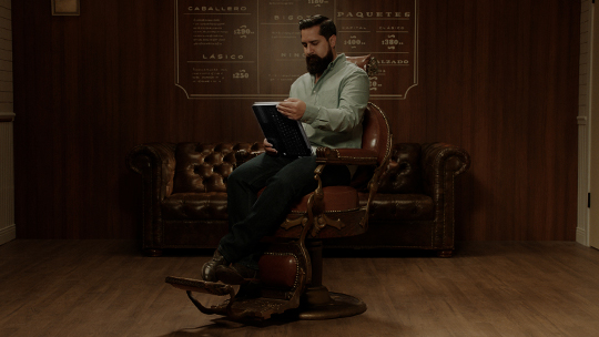 Marco sitting in a barbershop chair using the HP Pavilion x360 as a tablet.