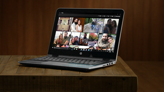 HP Pavilion x360 on desk in upright position with a photo gallery on screen.