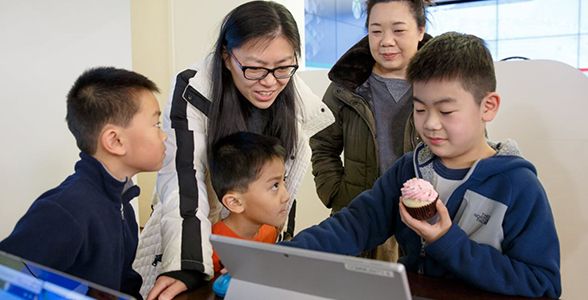 Family smiling while watching son eating a cupcake at the Cupcakes and Coding event at Microsoft Store.