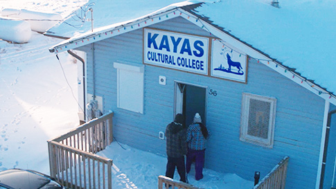 Exterior shot of building on Kayas Cultural College campus, with students outside.
