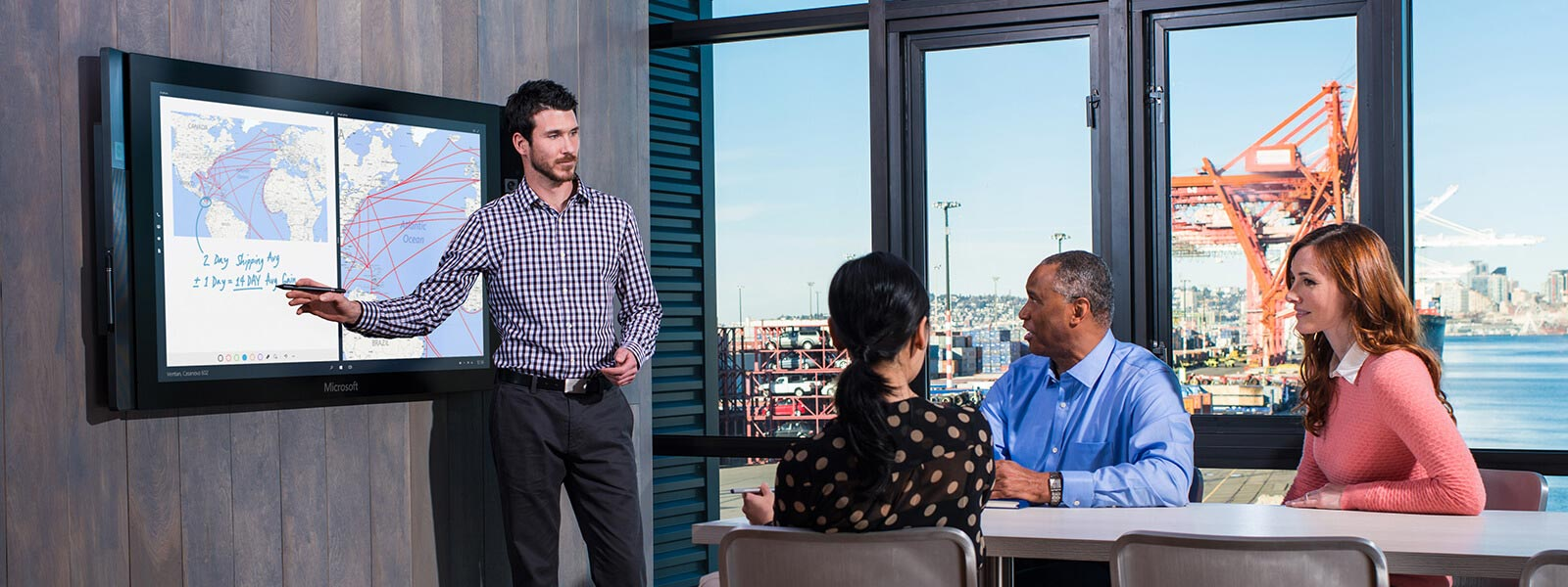 Man uses touchscreen on Surface Hub as he gives presentation in conference room.