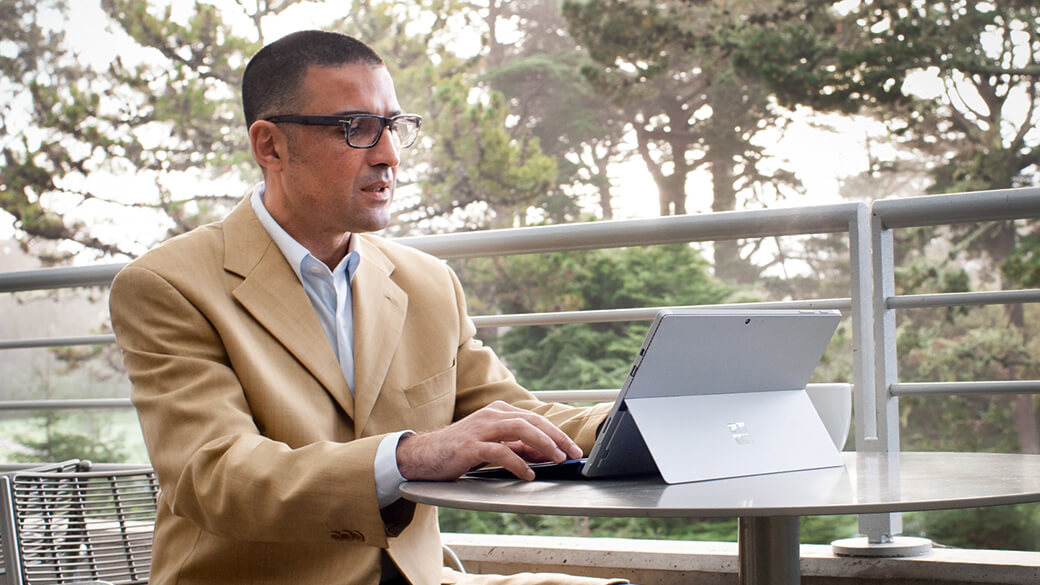 Man types on Surface Pro 4 at a table in an outdoor setting.