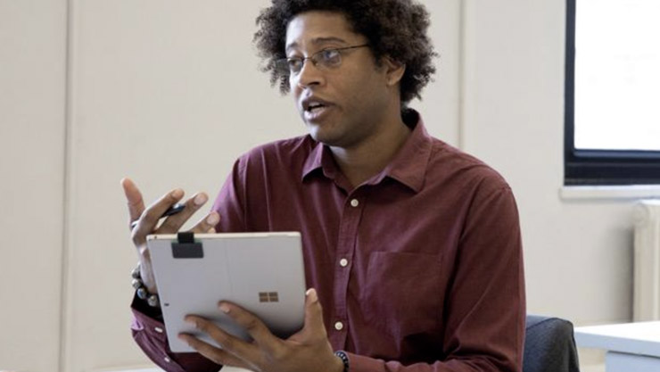 A caseworker holds Surface Pro (5th Gen) with LTE in Tablet Mode in one hand, and Surface Pen in the other hand