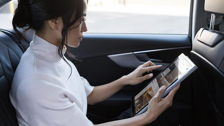 Woman sits in her car and uses her Surface device in tablet mode on the go