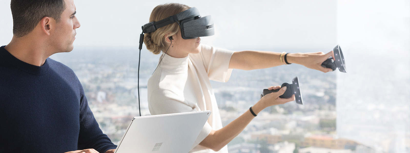 A man using a Surface Book 2 and a woman using a Windows Mixed Reality headset and motion controllers