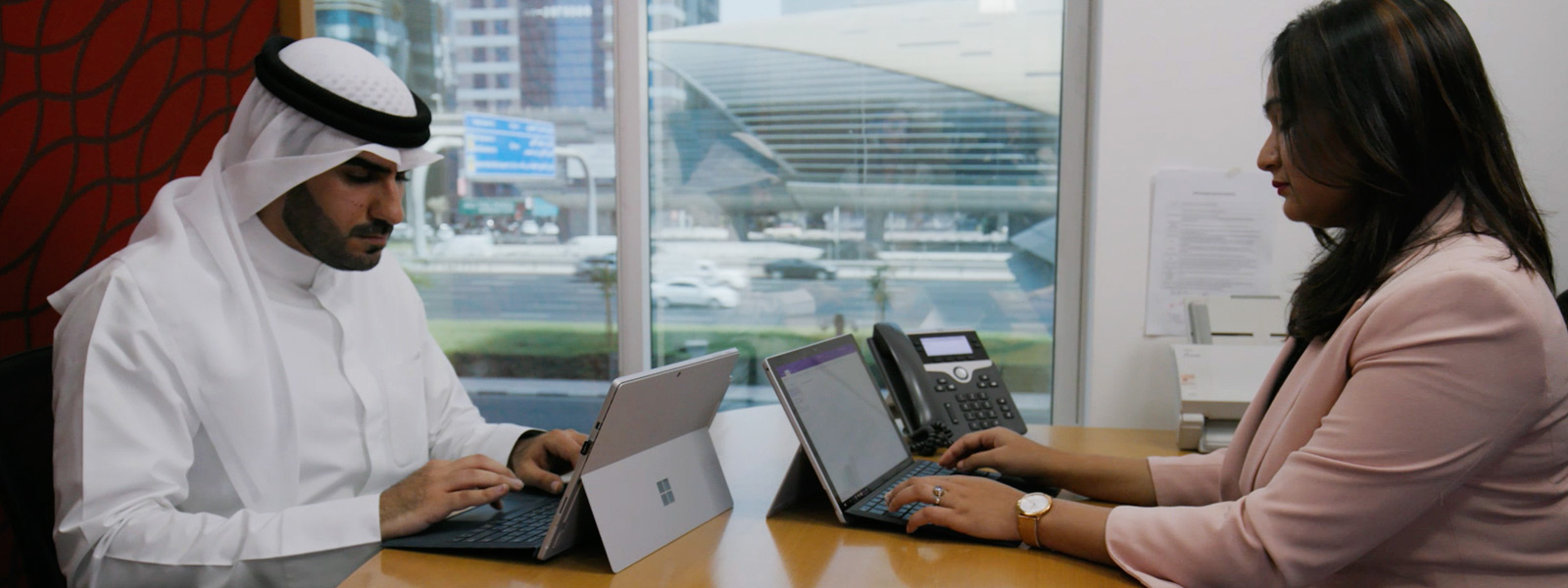 Two Mashreq employees work opposite each other on their Surface Pro devices.