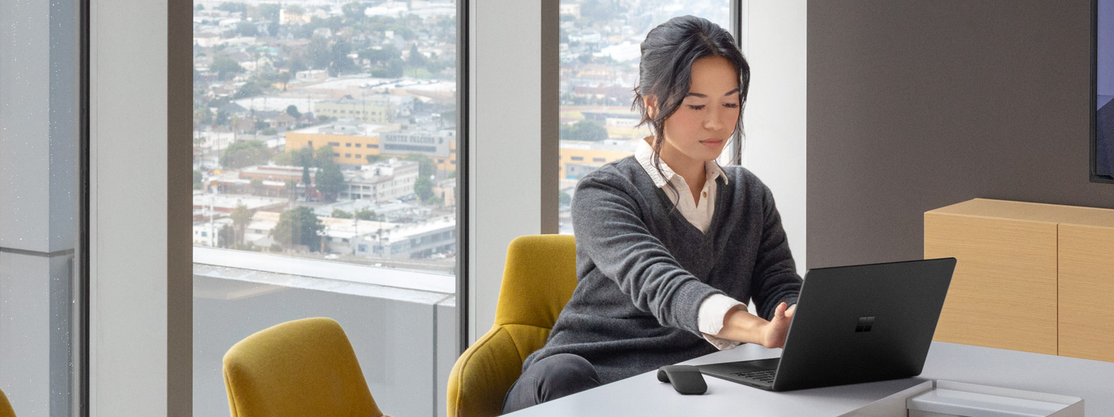 A woman works at her desk on her Surface Laptop 2 in matte Black
