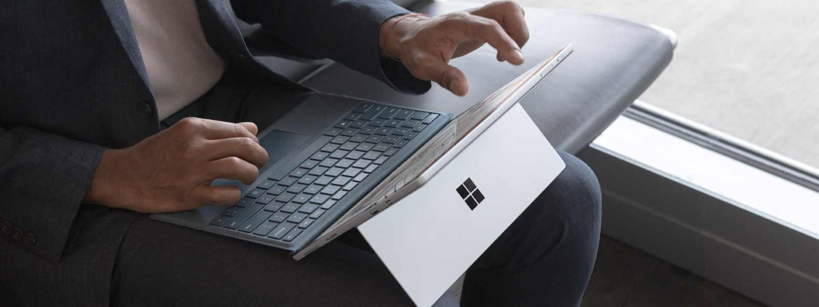 Two woman use Surface Book 2 with keyboard folded under in a café setting.