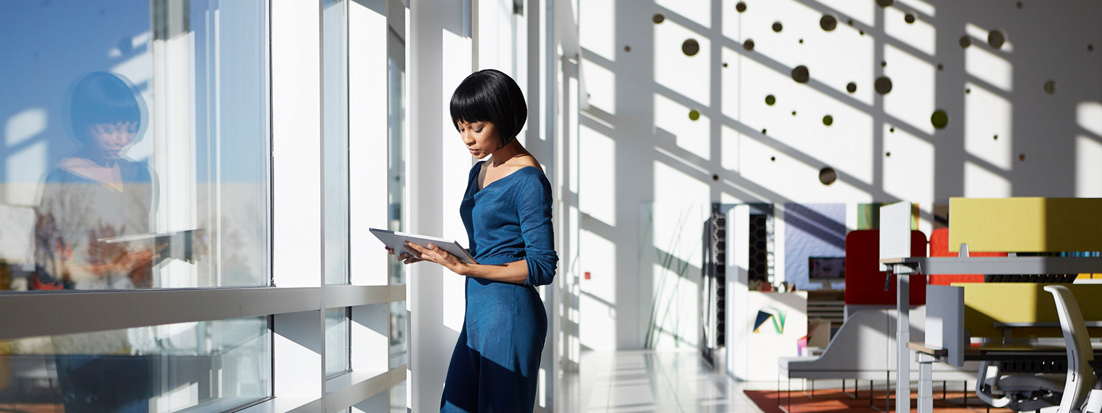 Woman using Surface Book in clipboard mode, standing in an office.