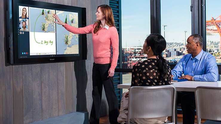 Woman giving presentation on Surface Hub in a conference room.