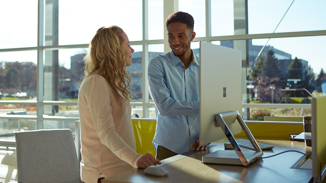 Man and woman look at Surface Studio in a Steelcase space.