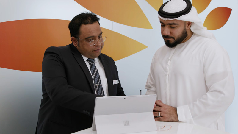 A Mashreq employee and his customer share information on a Surface Pro