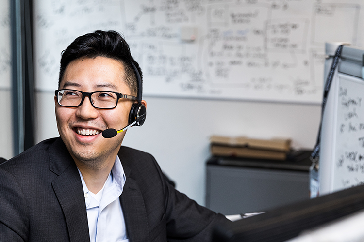 Person wearing glasses and sitting at a desk, wearing a headset