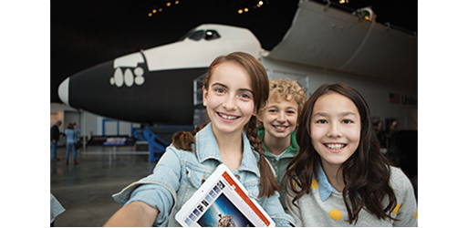 Three children smiling in front of an airplane, learn about collaborating with others in Office