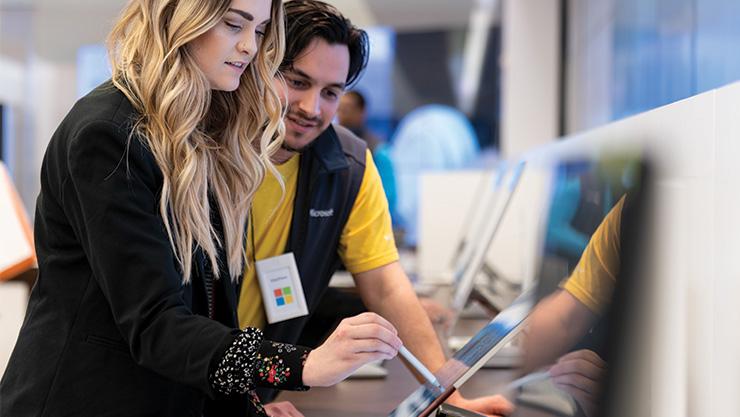 Microsoft Store associate helping customer on computer.