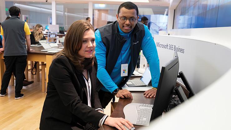 Microsoft Store associate helping customer on Surface device.