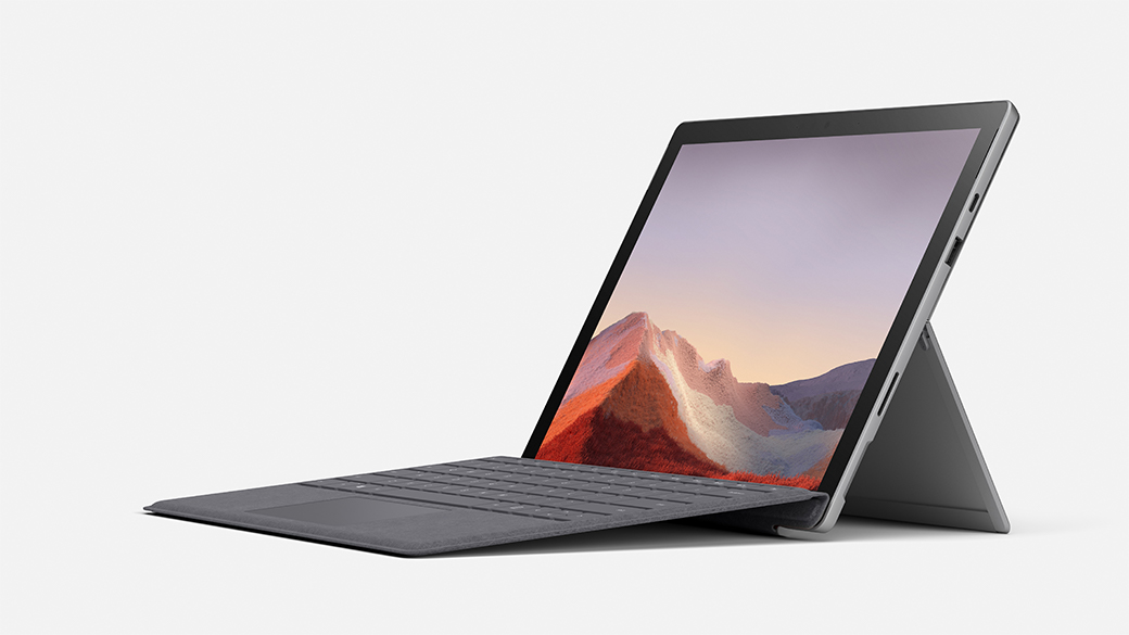 A Surface Pro 7 sits open with a landscape on the screen
