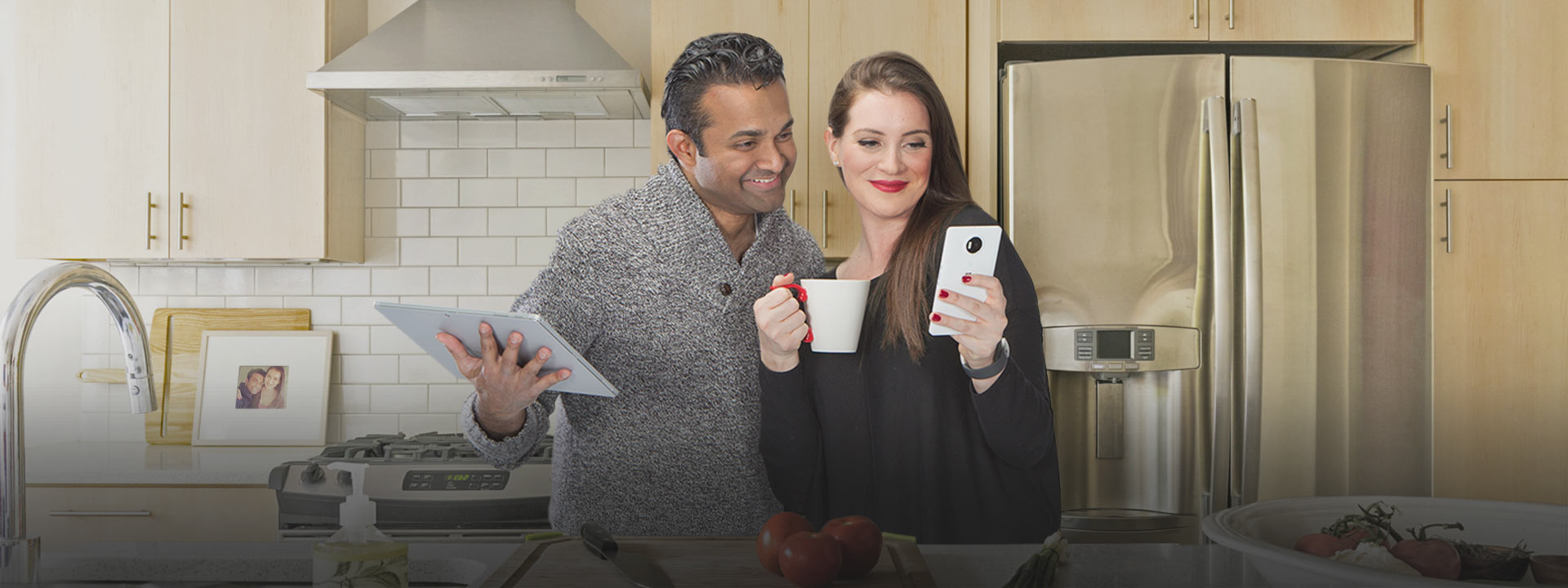 A couple standing together in a modern kitchen. The man is holding a tablet and the woman is holding a mobile phone. They are both smiling and looking at the screen on the mobile phone.