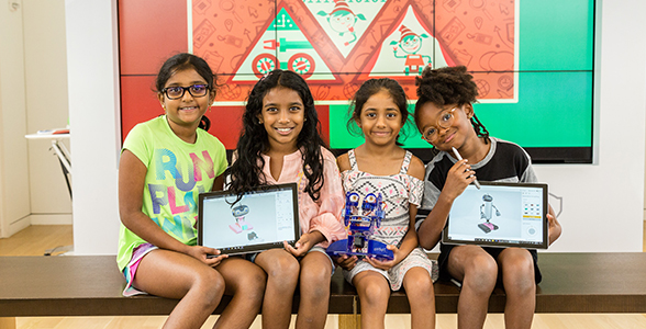 Four young girls sitting on bench holding Surface devices.