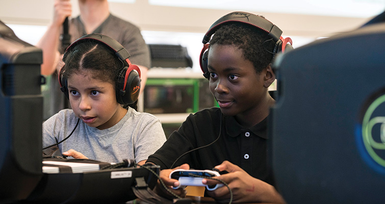 Female and male students gaming at Microsoft Store summer camp with headsets on.