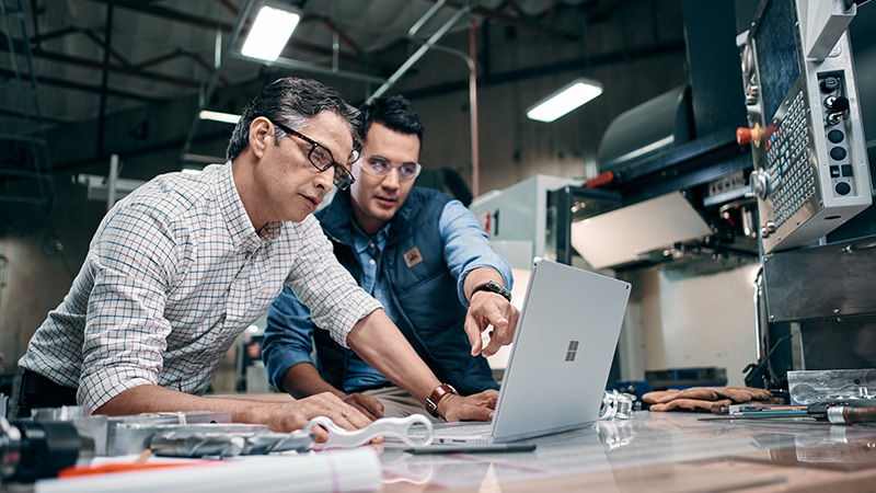 Two men look at a Surface Book.