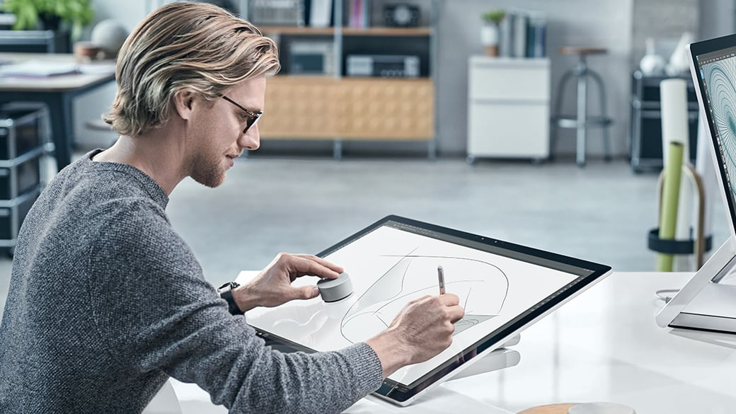 Man drawing on Surface Studio Screen while using dial in a modernoffice setting with another Surface Studio across from him