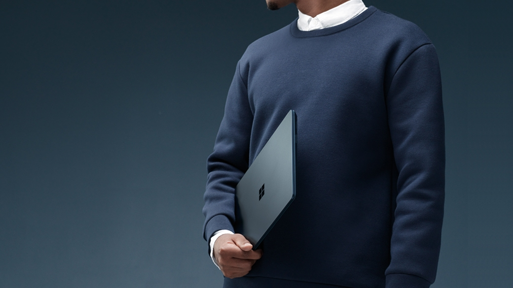Man holds a Cobalt Blue Surface Laptop in his right hand.