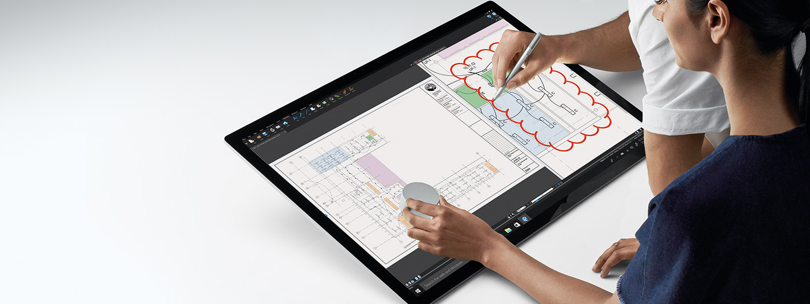 Two persons interacting with the Surface Studio with the Surface Dial and Surface Pen