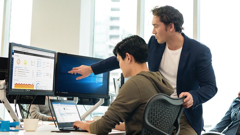 Two men reviewing the Windows Defender Center on dual screen desktop