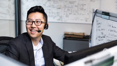 Man sitting in a cubical with a headset on