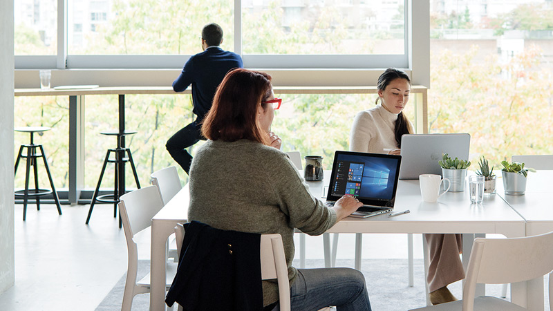 2 woman share a table while working on laptops